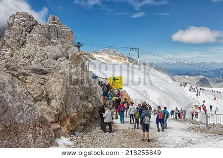 DACHSTEIN MOUNTAINS, AUSTRIA - JULY 17, 2017: People on top of Dachstein glacier waiting for entering a rope bridge between two mountain peaks