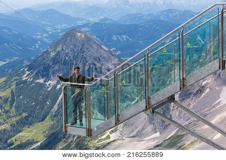 DACHSTEIN MOUNTAINS, AUSTRIA - JULY 17, 2017: Young man with thumbs up at view platform of skywalk rope bridge Dachstein Mountains in Austria