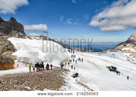 DACHSTEIN MOUNTAINS, AUSTRIA - JULY 17, 2017: Dachstein Mountain in Austria with hikers exploring the top of the glacier with machines preparing the ski piste