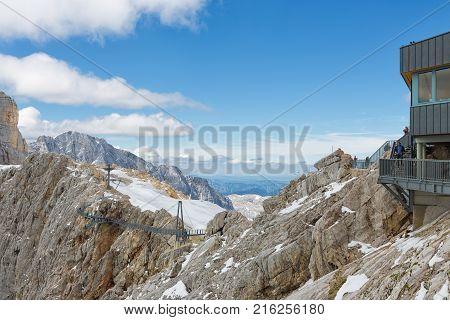 DACHSTEIN MOUNTAINS, AUSTRIA - JULY 17, 2017: Dachstein Mountain in Austria with hikers passing a steel skywalk rope bridge near the glacier top station