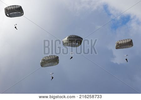 Four military paratroopers falling from the sky