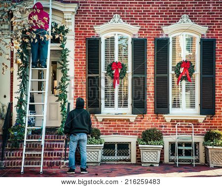 Workers hanging Christmas wreaths on a colonial home in northern Virginia.