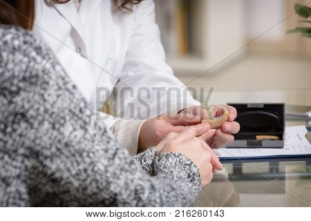 Doctor showing hearing aid to her patient in the doctor's office