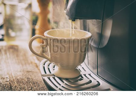 Coffee machine making fresh coffee with visible steam over cup.