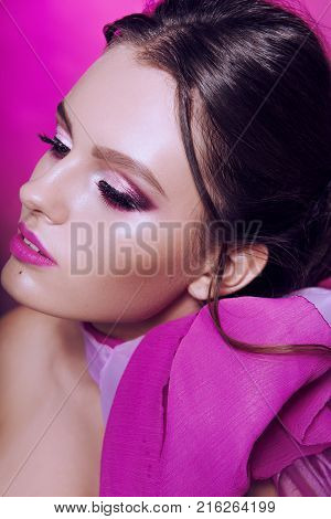 Beautiful Fashionable Girl Haired With Long Curly Hair Posing With A Pink Bow. The Girl In The Studi
