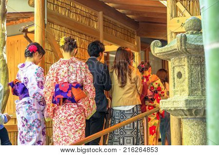 Kamakura, Japan - April 23, 2017: row of Japanese people in kimono at the entrance to green tea, for tea ceremony, a popular cultural activity in Japan. Hokoku-ji Take-dera Buddhist temple.