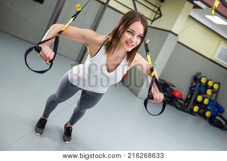 Young happy woman performs pushups with suspension straps, fitness workout at gym