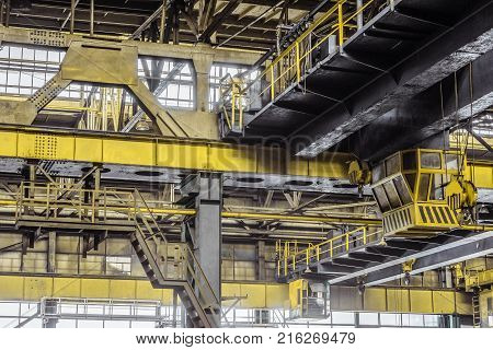 Overhead cranes with a crane operator cabin and hooks in a multi-span metal frame workshop. Steel landing pad.