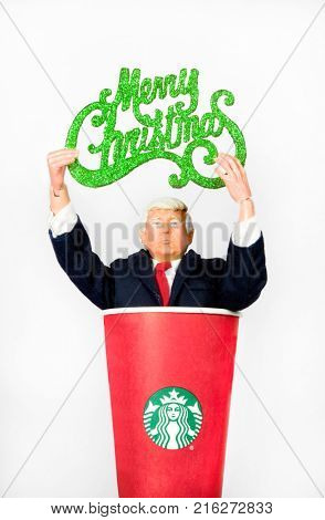 Donald Trump caricature action figure holding a Merry Christmas sign while coming out of a Starbucks coffee cup. Trump has waged a Twitter war with Starbucks over their holiday cups