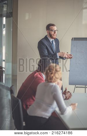 Confident handsome young businessman giving presentation using flipchart in office