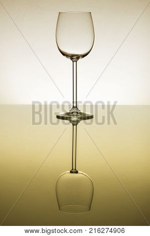 Empty wine glass standing on a reflective surface with a perfect reflection with yellow tint