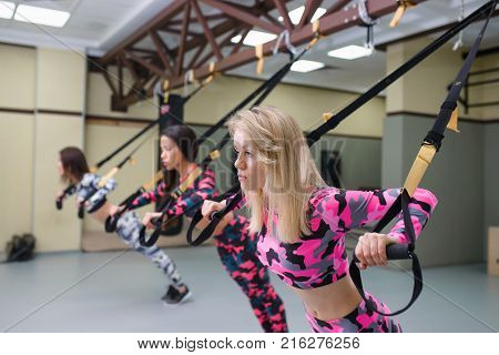 Women group performs pushups with suspension straps, fitness workout at gym, selective focus