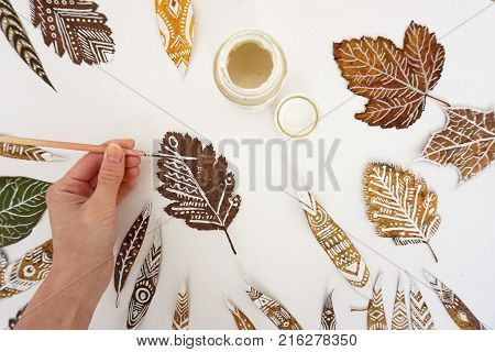 The process of painting on leaves. Many autumn dry leaves with ethnic patterns hand with a brush and a gouache can top view.