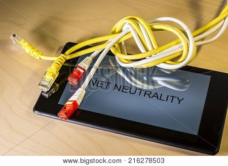 knotted net cable over a smartphone with the words Net Neutrality on screen. Suitable for concepts as net neutrality regulations, Internet Freedom Preservation Act , Open Internet order.