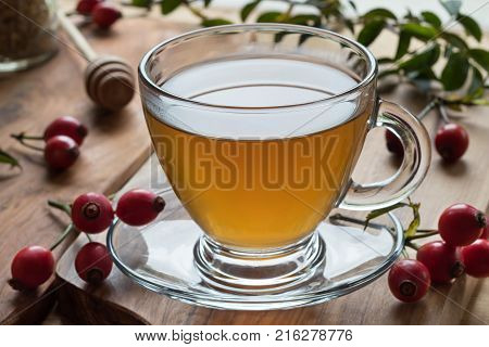 A cup of rose hip tea in contra light with fresh rose hips in the background