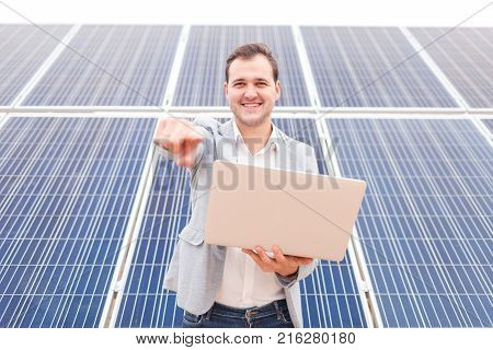 Happy handsome man in costume holding hands open modern laptop smiling and showing index finger in front of him, standing next to solar panels. Outdoors