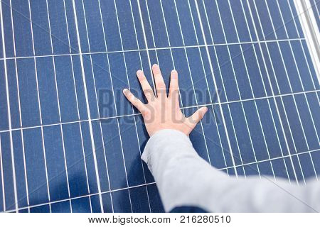 The hand of the European man lies on the panel of a modern solar battery. Outdoors.