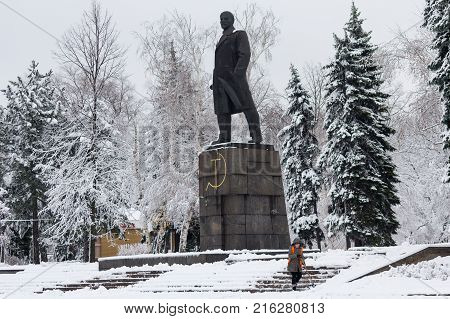 Makeevka Ukraine - November 22 2017: Woman in an orange waistcoat cleans the snow near the monument to the communist leader Lenin in a snow-capped city