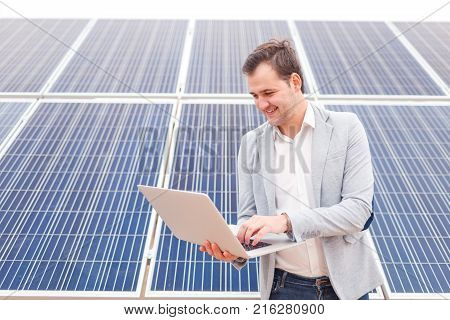 Smiling man working in a jacket holds in his hands an open modern laptop standing next to solar panels. Outdoors.