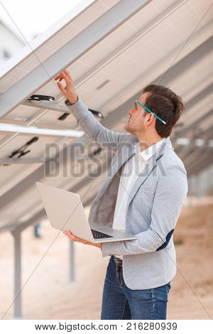 A man worker in a suit with a pencil behind his ear, holds a modern laptop in his hands and checks the solar panel. Outdoors