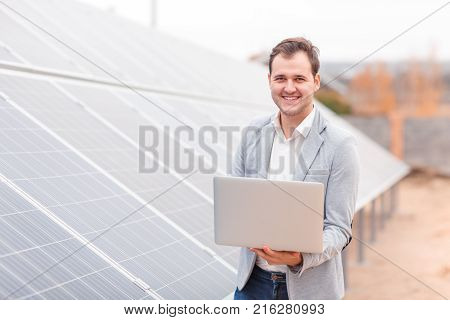 A smiling man, a solar cell employee, holds an open modern laptop in his hands standing next to the solar panel. Outdoors