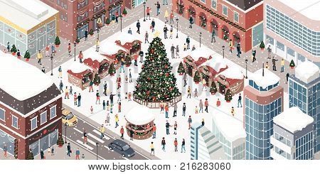 Happy people gathering together and celebrating Christmas in the city square around a tree under the snow