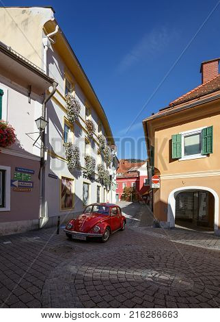 MURAU/ AUSTRIA - OCTOBER 7, 2017. Volkswagen beetle car on the beautiful one-way street in the historical town center of Murau. Styria, Austria.
