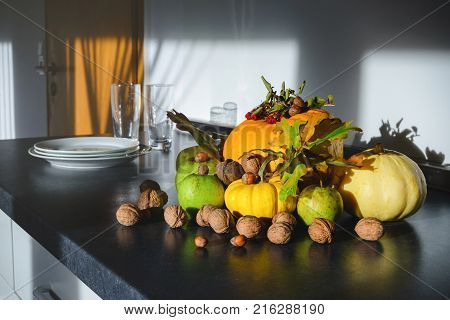 Orange and yellow pumpkins, green farm apples, wall nuts and a glass of cow milk on the table maikng a beautiful embient autumn still life composition in kitchen