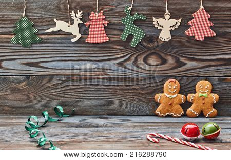 Christmas homemade gingerbread cookies and decoration on wooden background. Gingerbread couple - man and woman.