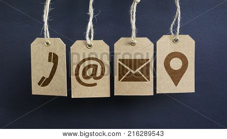 Website contact us icons on hanged paper tags with email at telephone and location pin symbol.