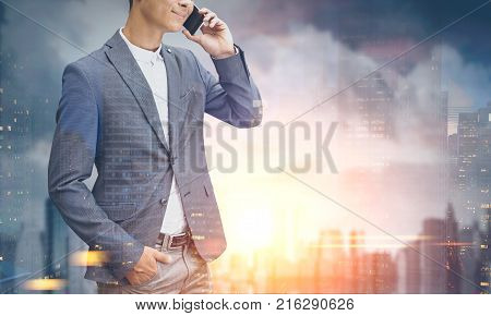 Portrait of a young unrecognizable businessman in a suit talking on the phone and smiling. He is standing against a morning city background. Toned image mock up