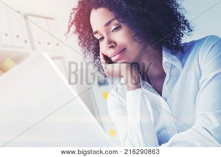 Portrait of a pensive beautiful African American businesswoman in a white shirt looking at her laptop screen. Toned image