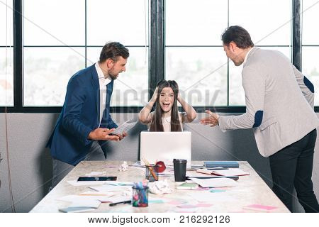 Two men threateningly scream at a young girl, and frantically clinging to her head, crying hysterically and screaming. Inside the office.