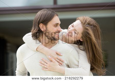 Young couple in love laughing having fun together, loving smiling wife embracing husband from his back outside house, man and woman looking at each other enjoying leisure spending time outdoors