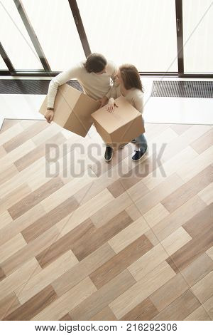 Happy young couple coming into big modern house holding boxes, smiling married man and woman moving in new home with belongings, buying real estate, mortgage loan and relocation, top view
