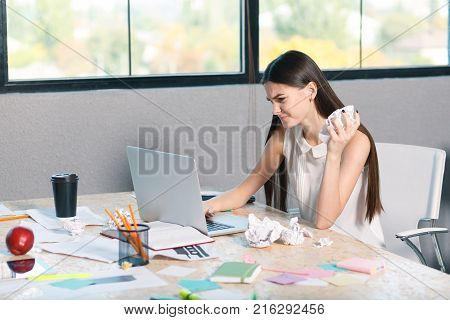A frustrated, angry young girl is working behind a laptop and is sucking paper documents behind her nerves. Inside the office.