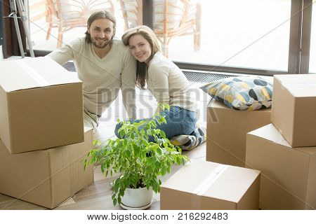 Moving day, happy couple looking at camera sitting on the floor bonding with boxes belongings, young first time homeowners enjoying new home, buying real estate, move in out and relocation concept