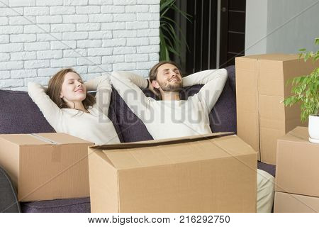 Happy couple relaxing on sofa with boxes, relaxed man and woman resting on couch hands behind head on moving day, dreaming of future in new own home, delivery service for easy move concept