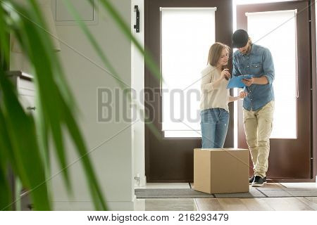 Young woman receiving cardboard box from courier at home, receiver about to sign document for accepting parcel, man with clipboard delivering package to customer, door delivery service concept