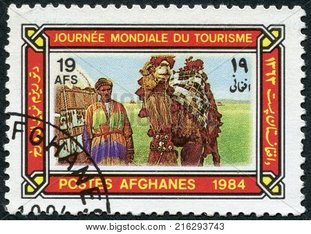 AFGHANISTAN - CIRCA 1984: A stamp printed in the Afghanistan devoted to World Tourism Day. Depicted Camel driver, tent, camel in caparison, circa 1984
