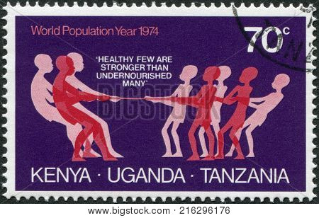 EAST AFRICAN COMMUNITY - CIRCA 1974: A stamp printed in East African Community, is dedicated to World Population Year, shows a tug of war with the malnourished, circa 1974