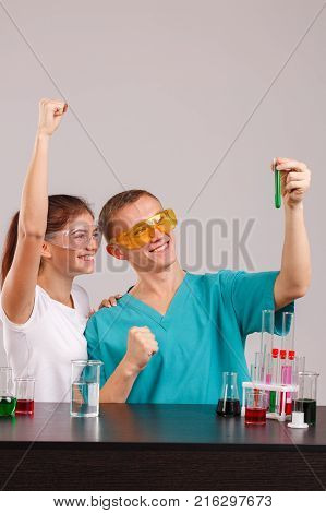 Two happy young laboratory assistants in uniform and special glasses, are bursting with a successful experiment, holding a small glass flask with a green liquid. Indoors laboratory. Isolation.