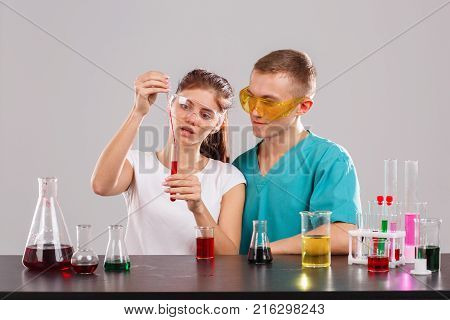 Two young laboratory assistants in special glasses and uniforms, the girl pours a red liquid from a measuring pipette into a glass stake. Indoors laboratory. Isolation....