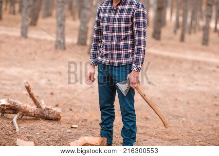 A man in a plaid shirt, a woodcutter stands in a forest among the trees and holds an ax in his hands. Outdoors.