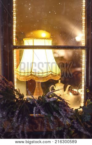 Cosy view to the window and the room inside (with a lamp flowers and teapot) from the street of Prague.