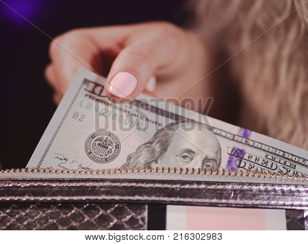 pretty fingers of woman holding money close up with purse, luxury jewellery on python clutch, cash for gifts