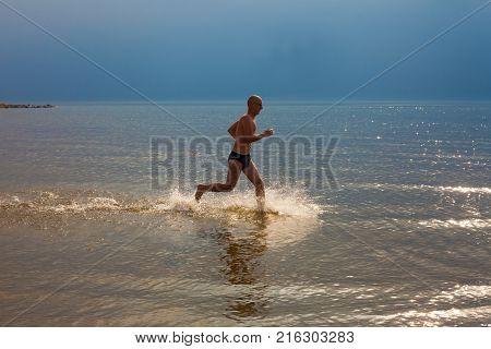 Man Runs Along The Sea