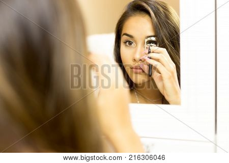 Reflective on mirror mixed race woman making curl eyelashes using curling make up accessory