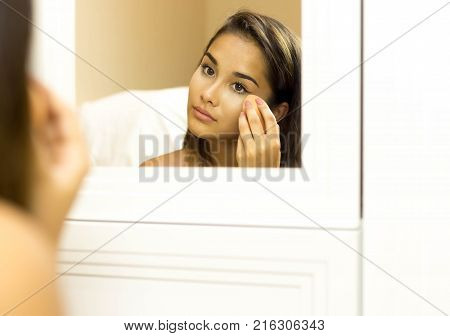 Reflective mixed race young woman applying foundation on with sponge looking in the mirror