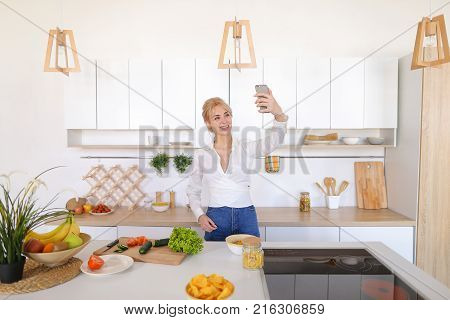 Marvelous girl housewife with smartphone communicates by video call with husband and greets with hand, with smile on face shows what she preparing for dinner and directs camera to cucumbers and tomatoes